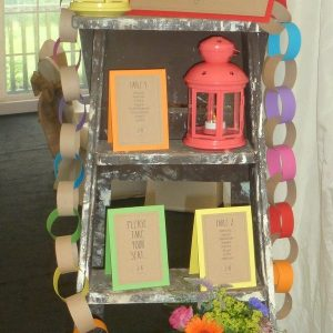 colourful carnival theme table plan on a vintage ladder