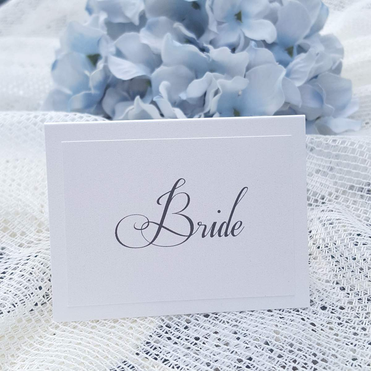 Elegant white wedding place card with Bride printed in a fancy calligraphy font