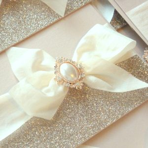 bows and bling invitation in blush with rose gold pearl