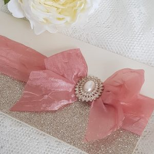 wedding invitation with rose gold ribbon and pearl