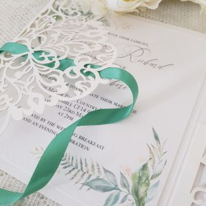 laser cut pocketfold invitations with pretty greenery print