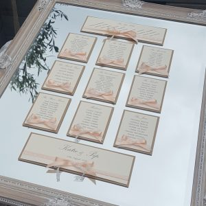 mirror wedding table plan with peach ribbon and lace