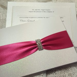 pocketfold wedding invitation with white glitter and hot pink ribbon