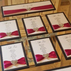 navy, silver and magenta wedding mirror table plan with diamante hearts