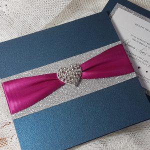 navy wedding invitation with silver glitter, magenta ribbon and diamante heart