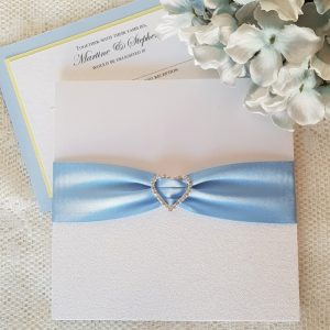 white glitter wedding invitation with blue ribbon and diamante heart buckle