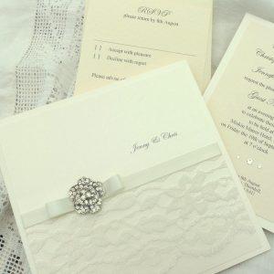 vintage lace wedding invitation with rose diamante brooch invitation