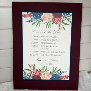 wedding order of the day board with a burgundy floral design