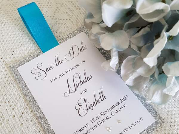 Bookmark style wedding save the date card with blue ribbon and silver glitter