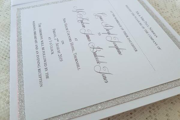 white and silver wedding invitation showing details