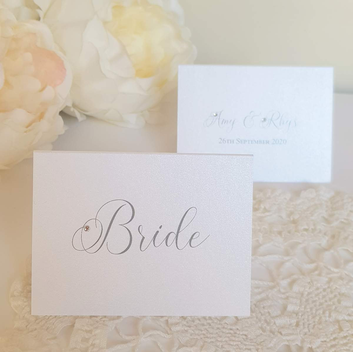 Elegant white wedding place cards with crystals