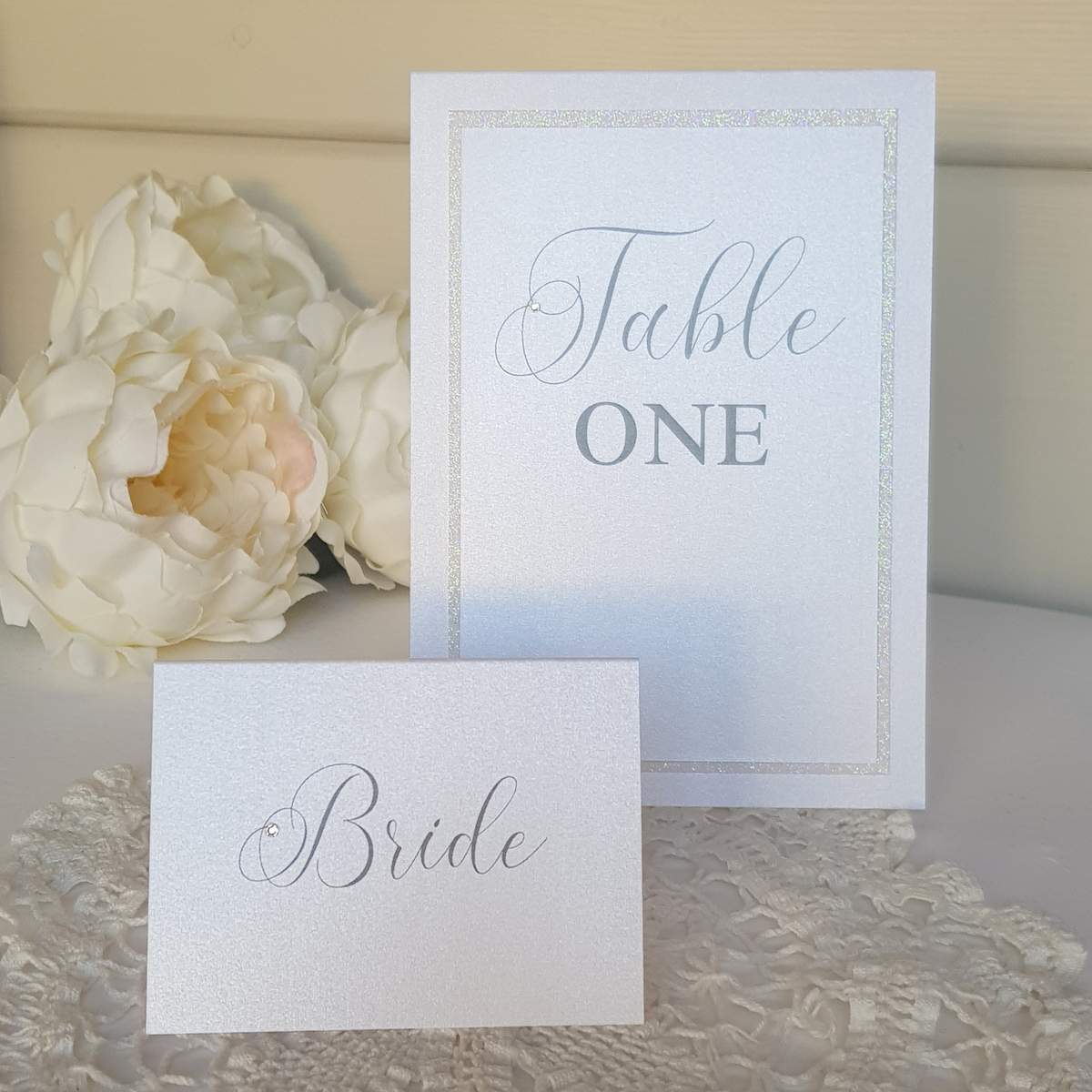Elegant white wedding table stationery, a place card and table number
