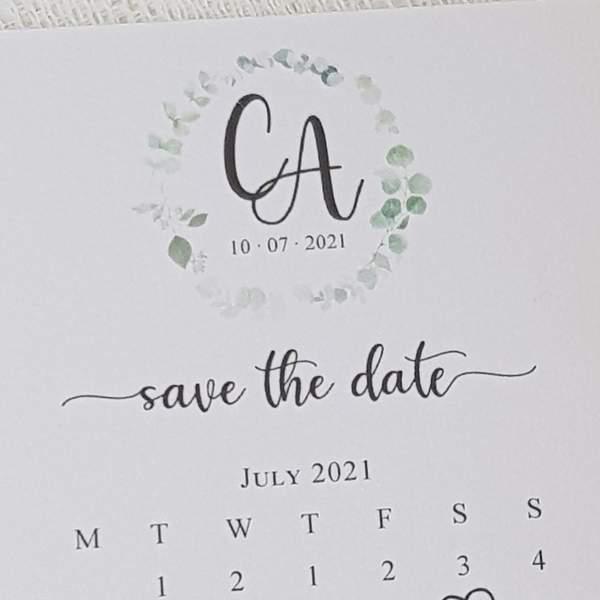 calendar style wedding save the date cards with eucalyptus wreath design