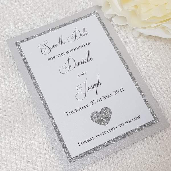 save the date card with silver glitter heart design