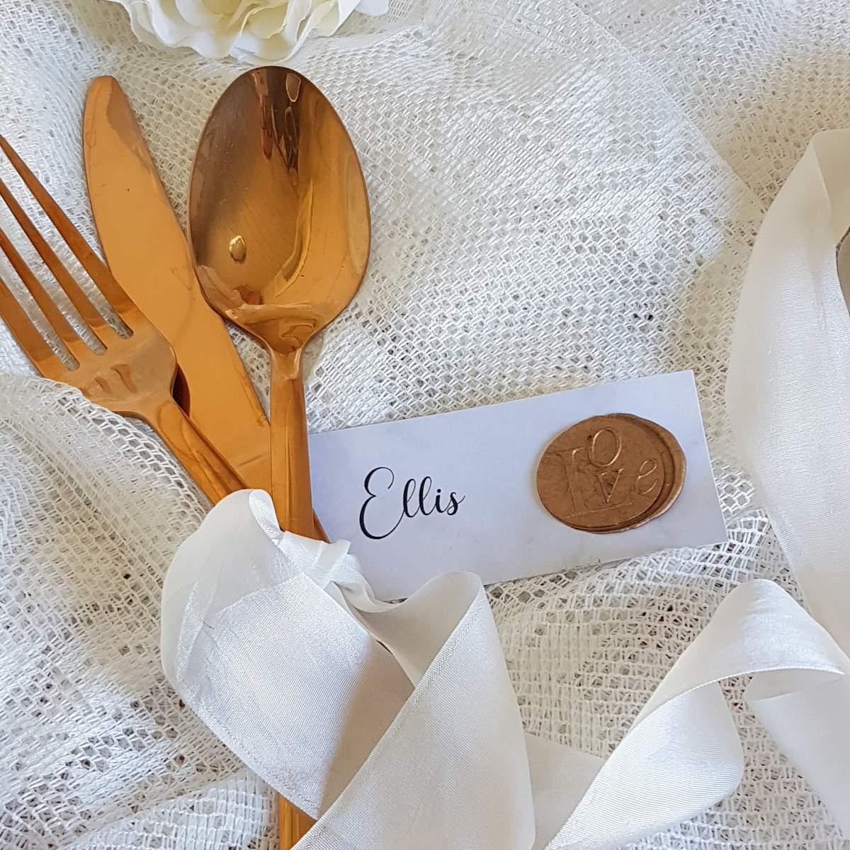 White wedding place card with calligraphy and gold wax seal