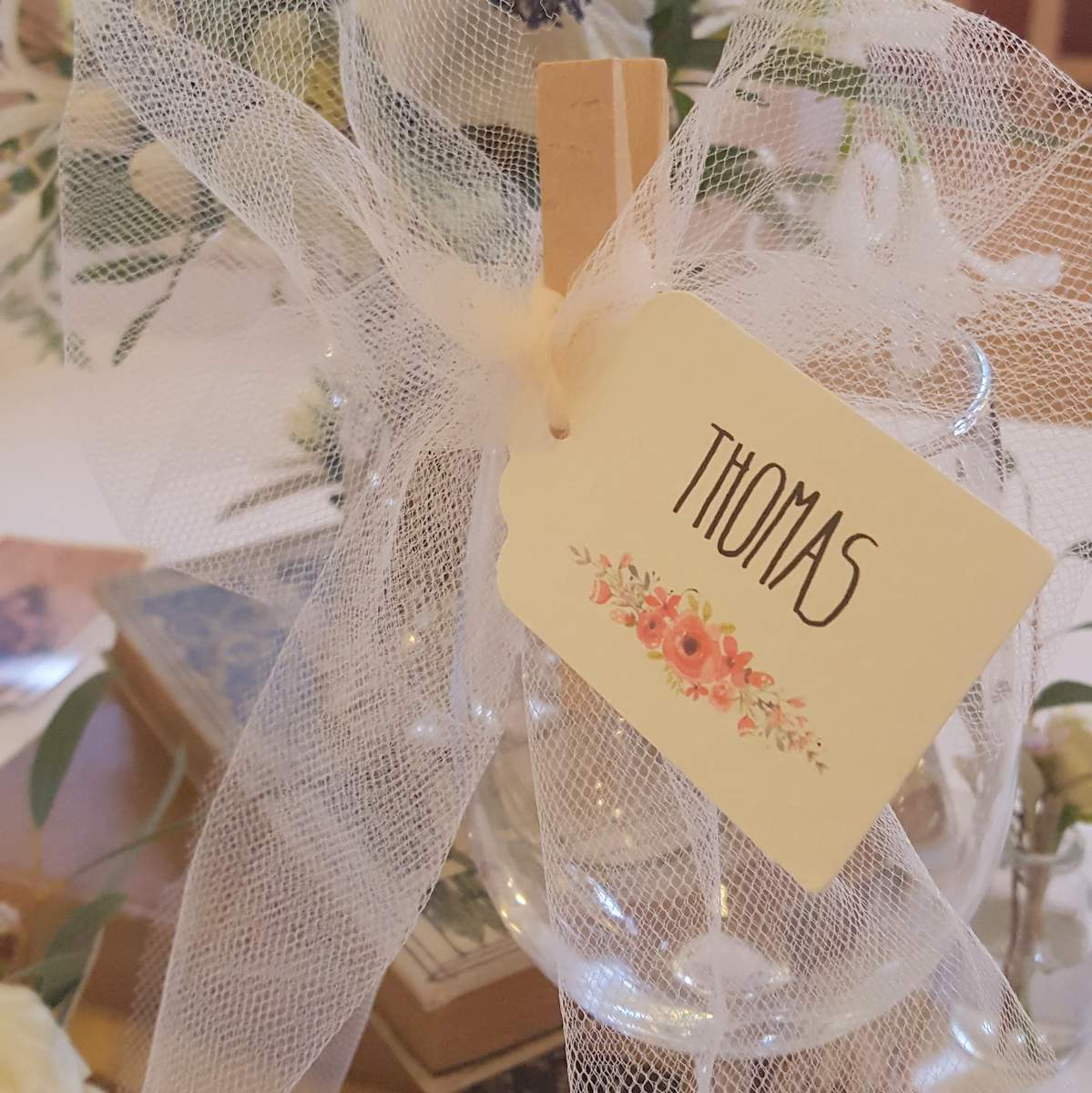 place tag with pink roses pegged to wine glass with a white tulle bow