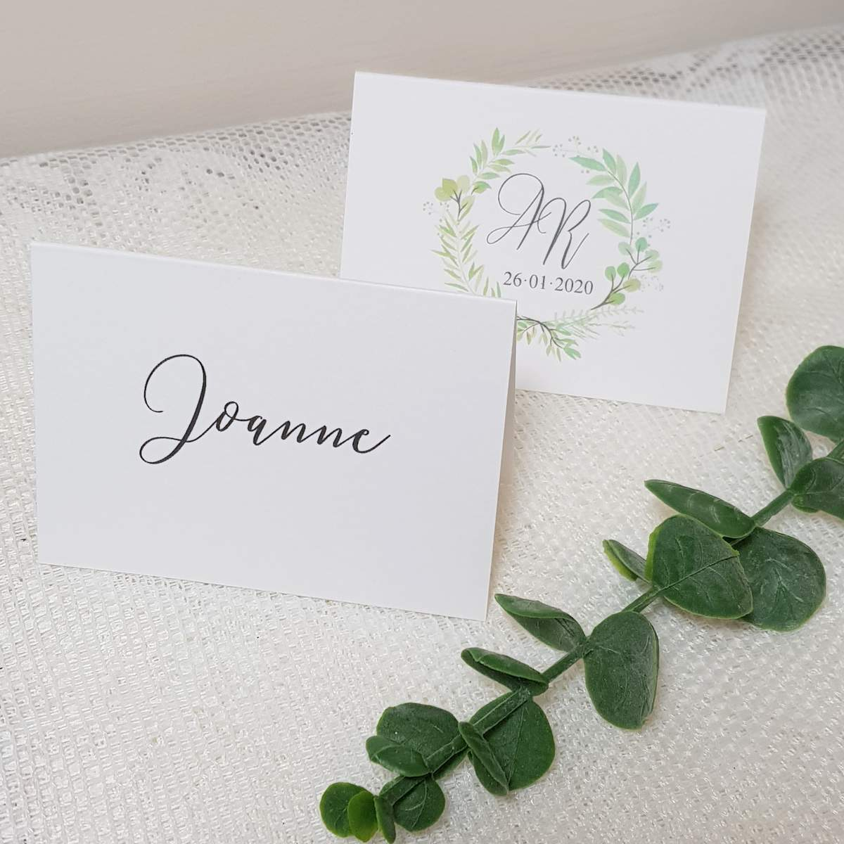 white place cards with a greenery wreath design