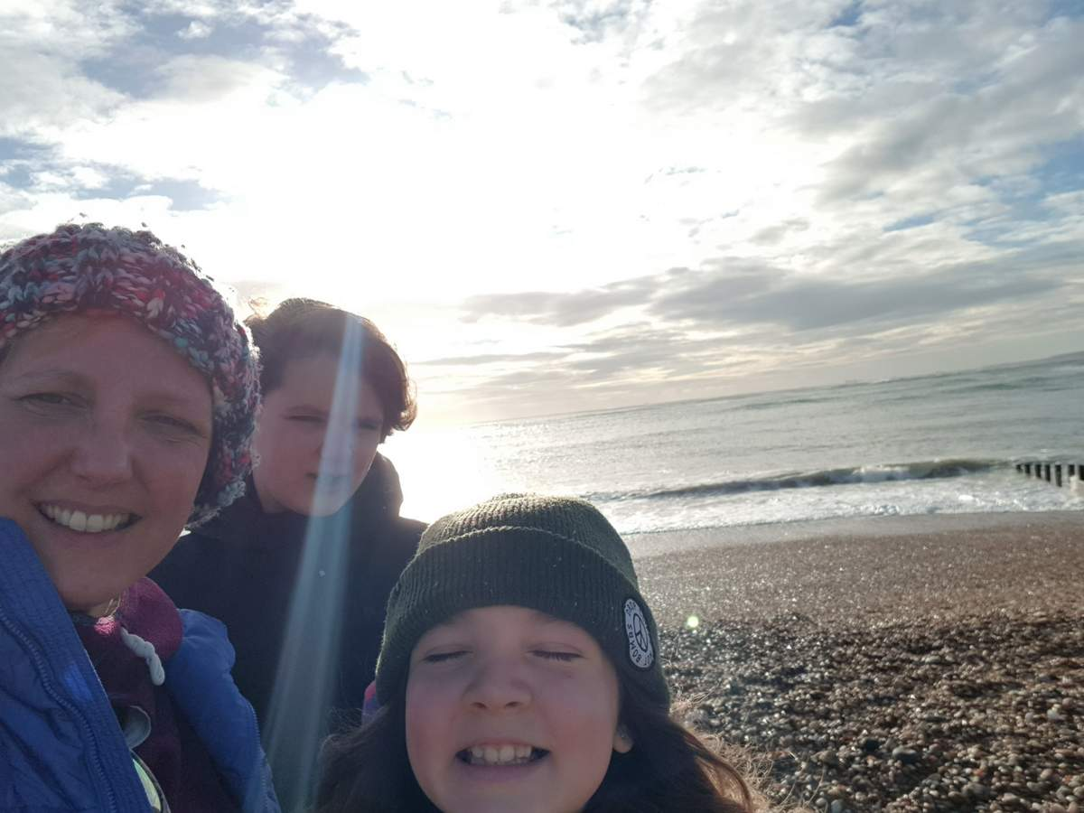 a mum and her daughters at the beach in winter