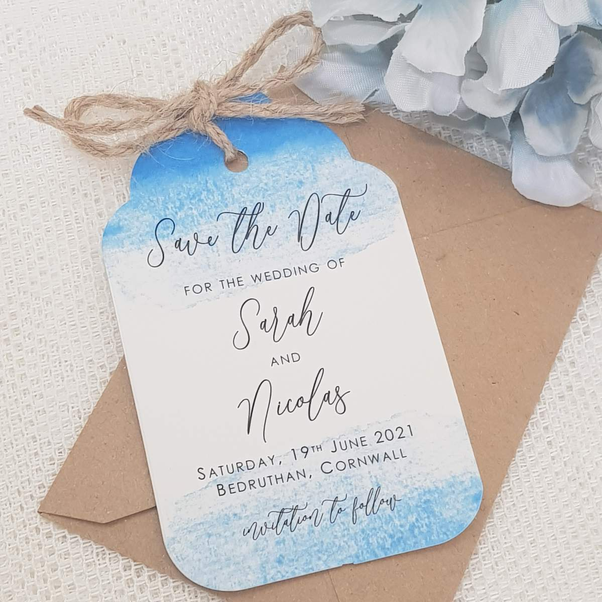 Luggage tag style save the date card with a blue watercolour print, tied with natural twine
