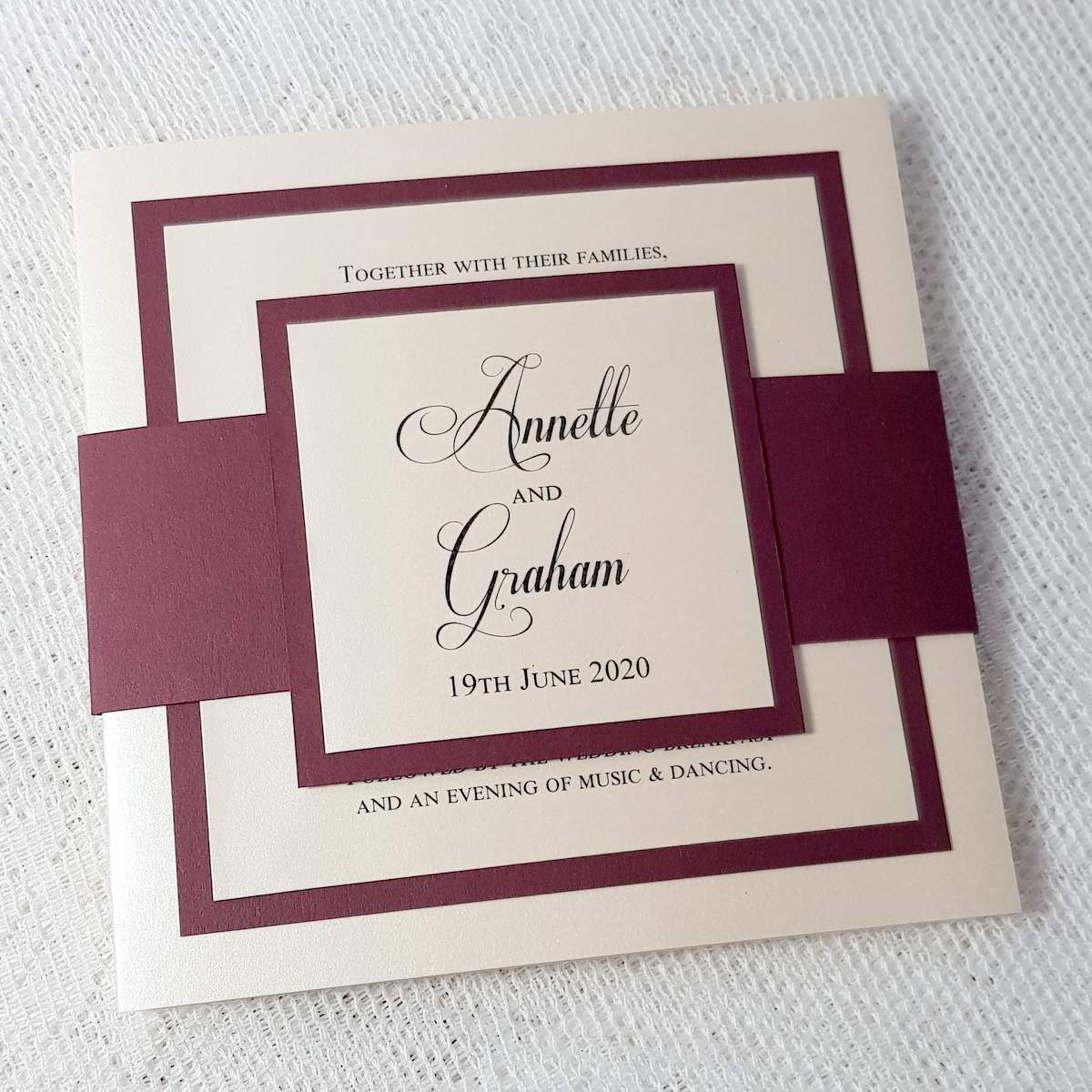 ivory concertina invitation with a burgundy border and bellyband