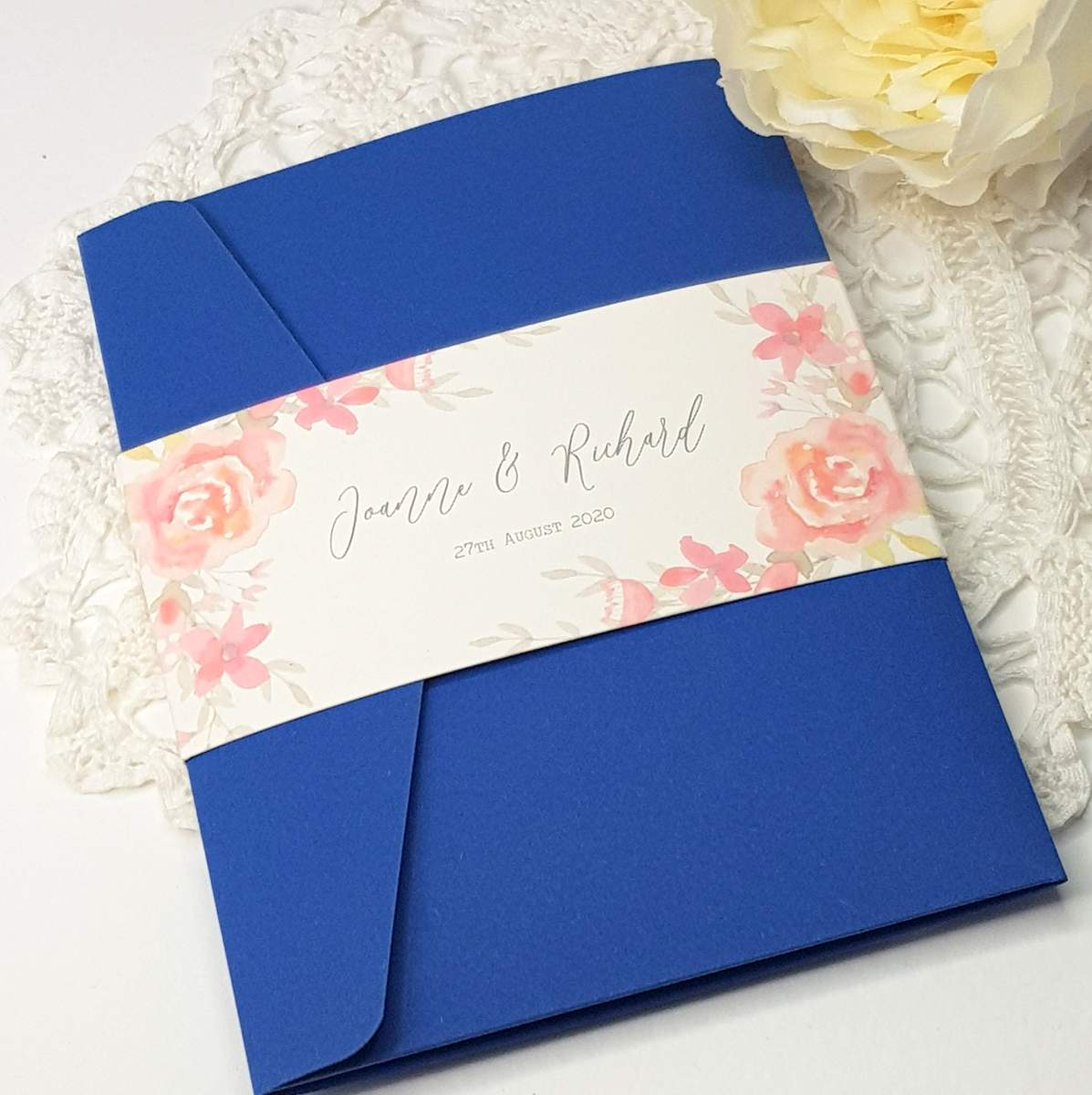 blue pocketfold wedding invitation with a bellyband featuring coral roses
