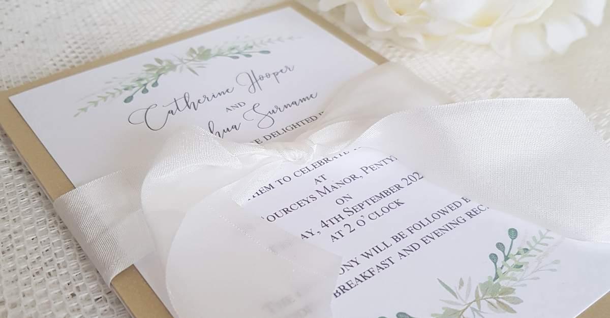 An elegant flat wedding invitation with a greenery design print and silk ribbon
