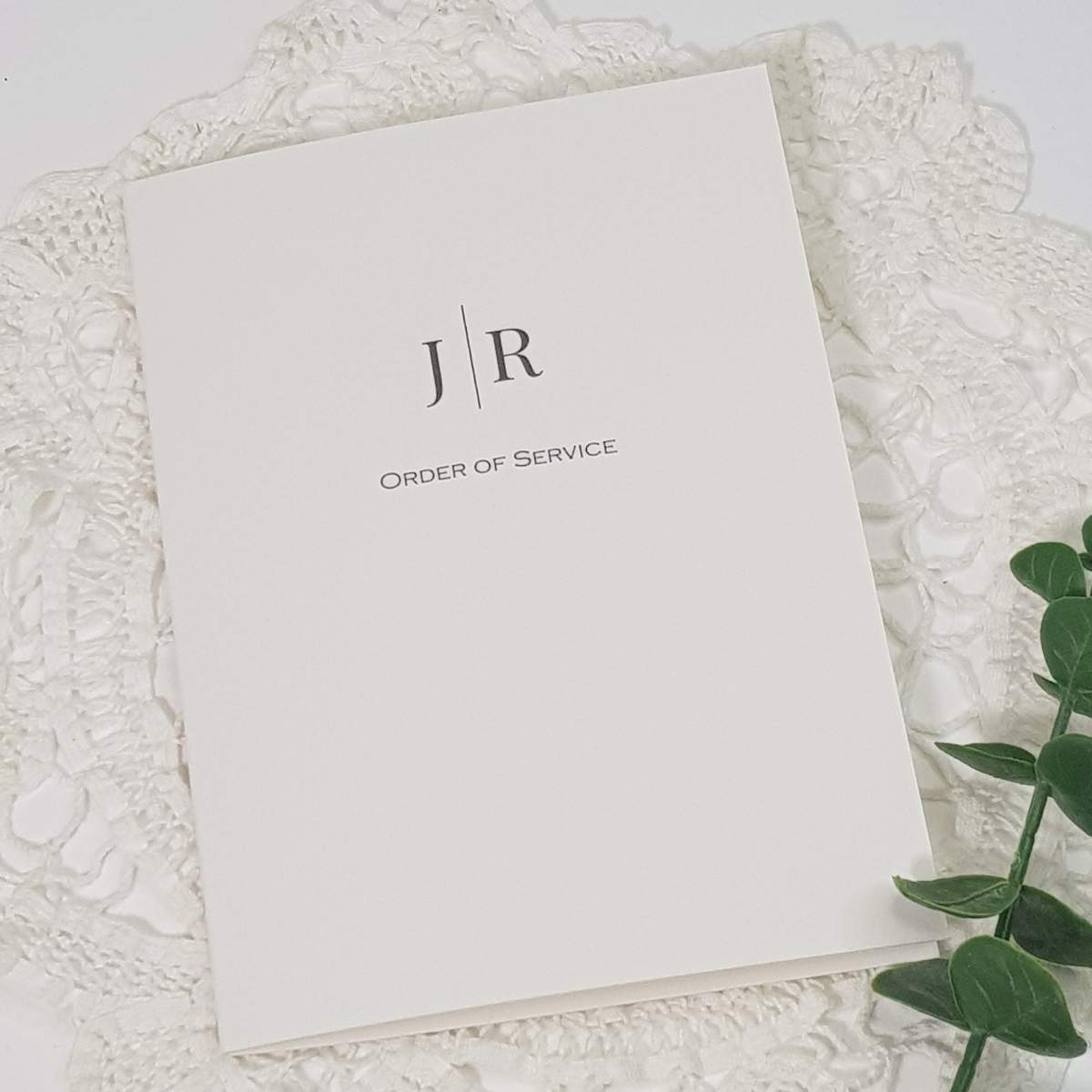 white wedding order of service with a contemporary monogram design
