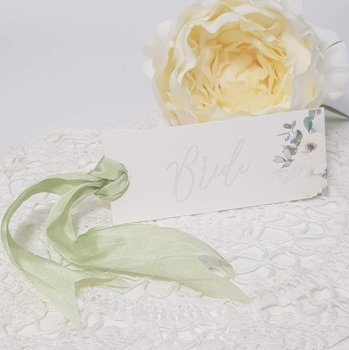 Wedding place name tag with white flowers and pale green silk ribbon