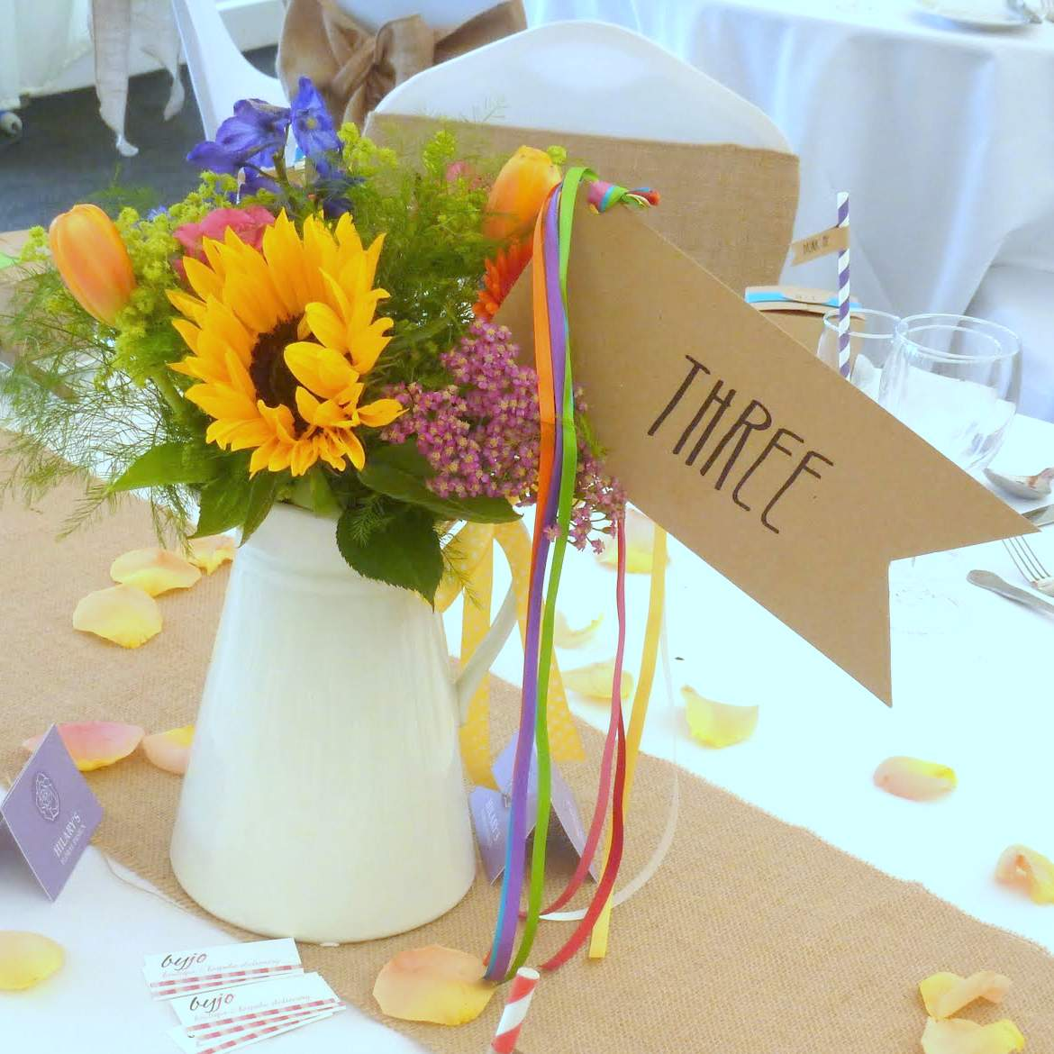 rustic wedding table number flag with rainbow ribbons