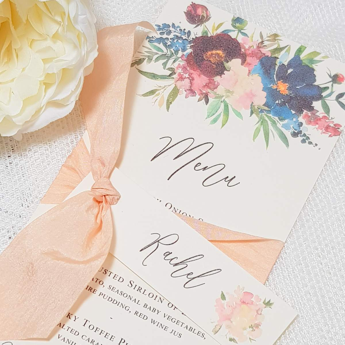 wedding menu with floral design and peach silk ribbon