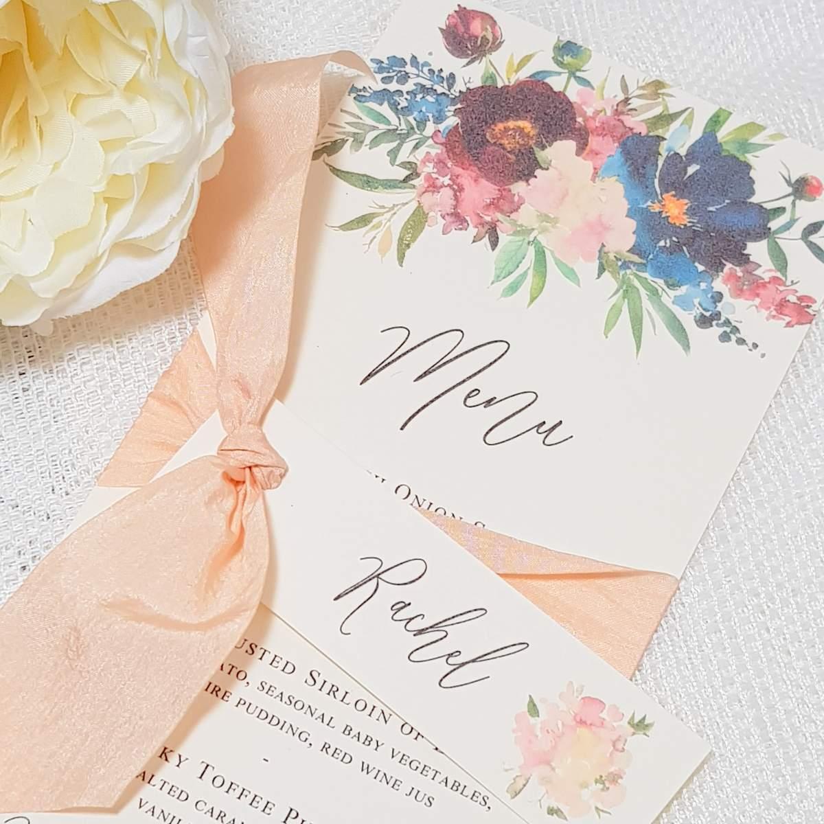 wedding menu with floral design and peach silk ribbon