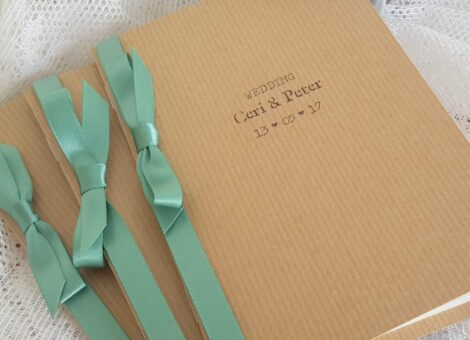 rustic kraft wedding order of service with a sage green satin ribbon for decoration