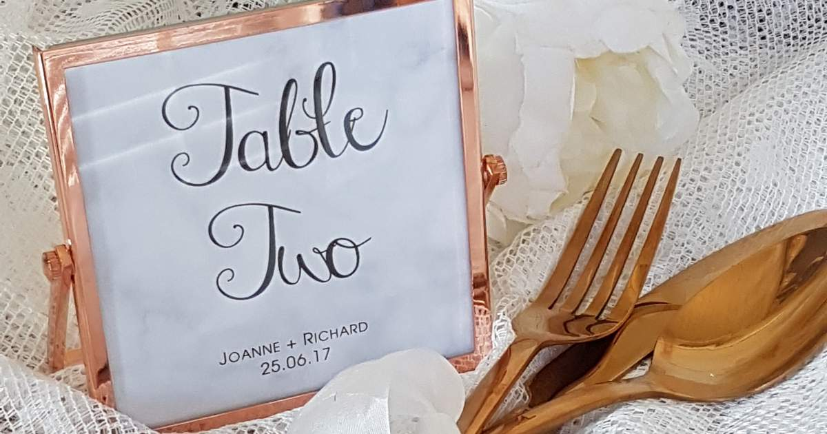 calligraphy wedding table number in a rose gold frame