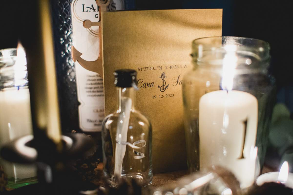 A rustic, nautical theme wedding table setting with candles and bottles