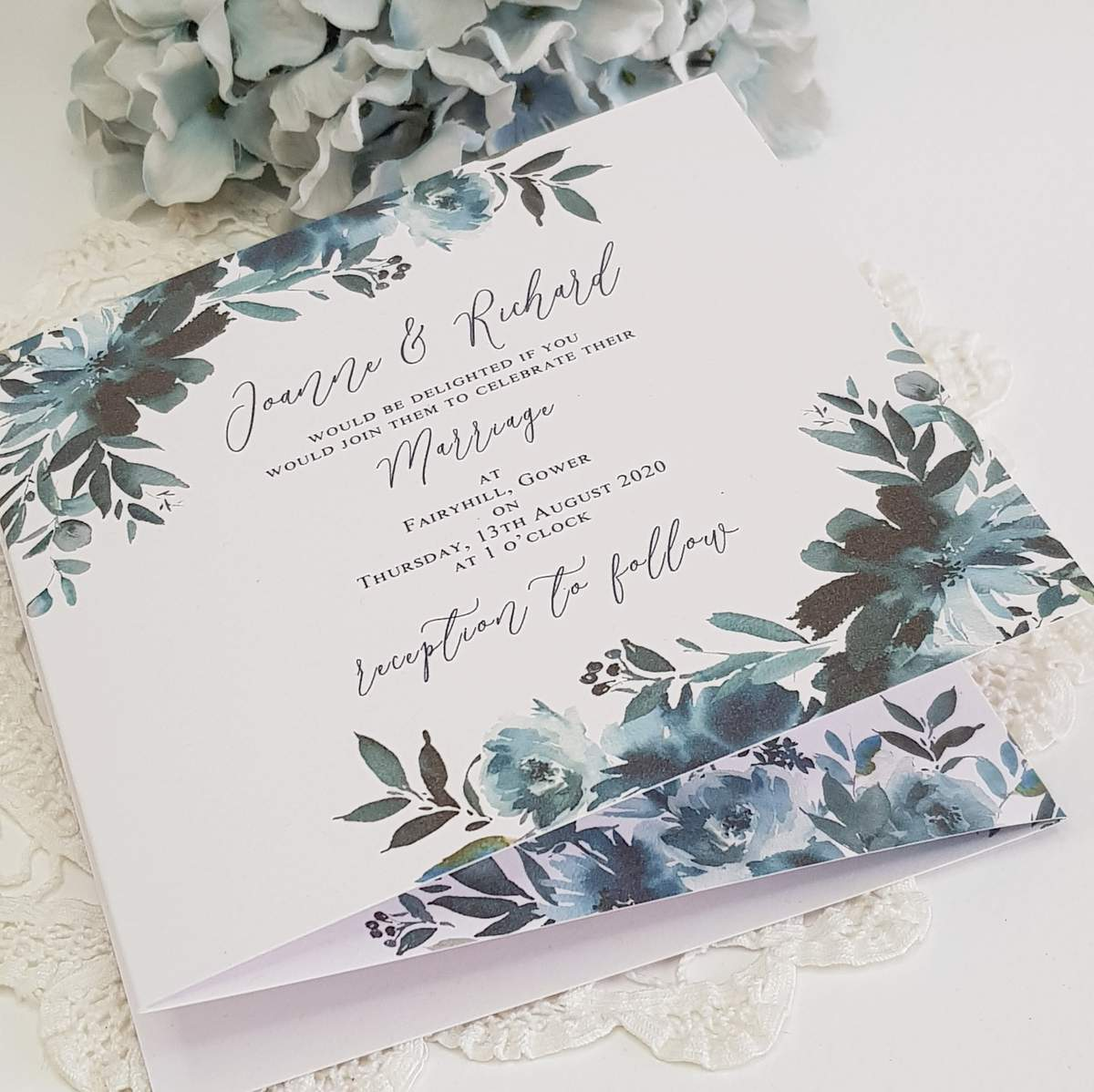 concertina style wedding invitation with a navy blue floral design