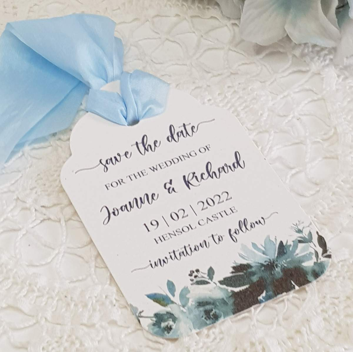 luggage tag style save the date card with a navy floral design and pale blue silk ribbon