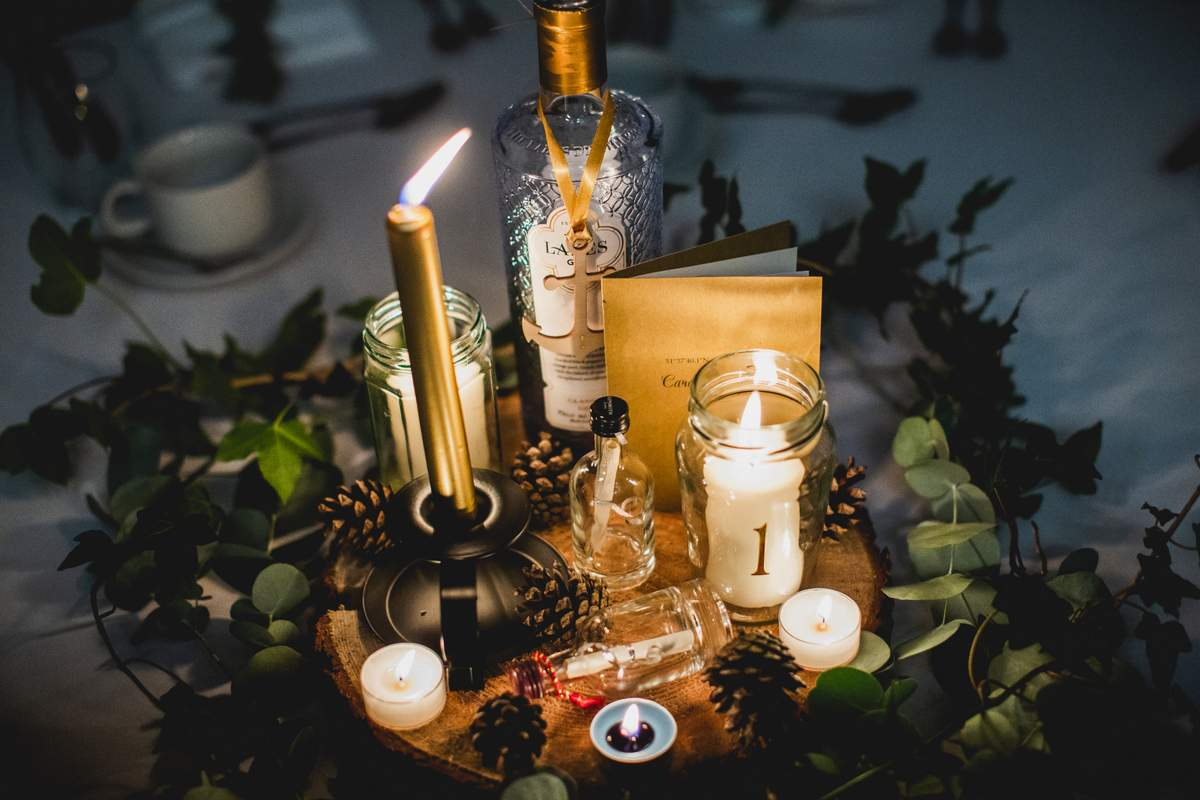 A rustic, nautical theme wedding table setting with candles, a log slice and greenery