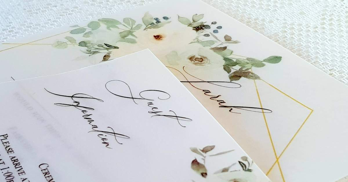 pretty wedding invitations with pale green and white flowers printed on vellum