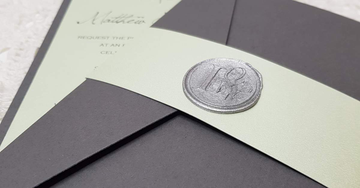 A pale green bellyband with a wax seal, around a dark grey pocketfold wedding invitation