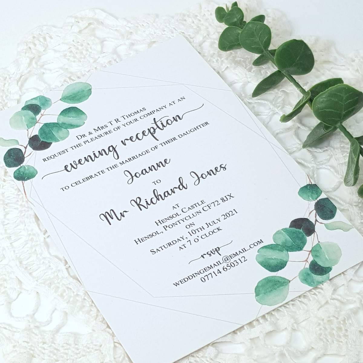 A flat evening wedding invitation with a modern calligraphy style font and eucalyptus design accents.