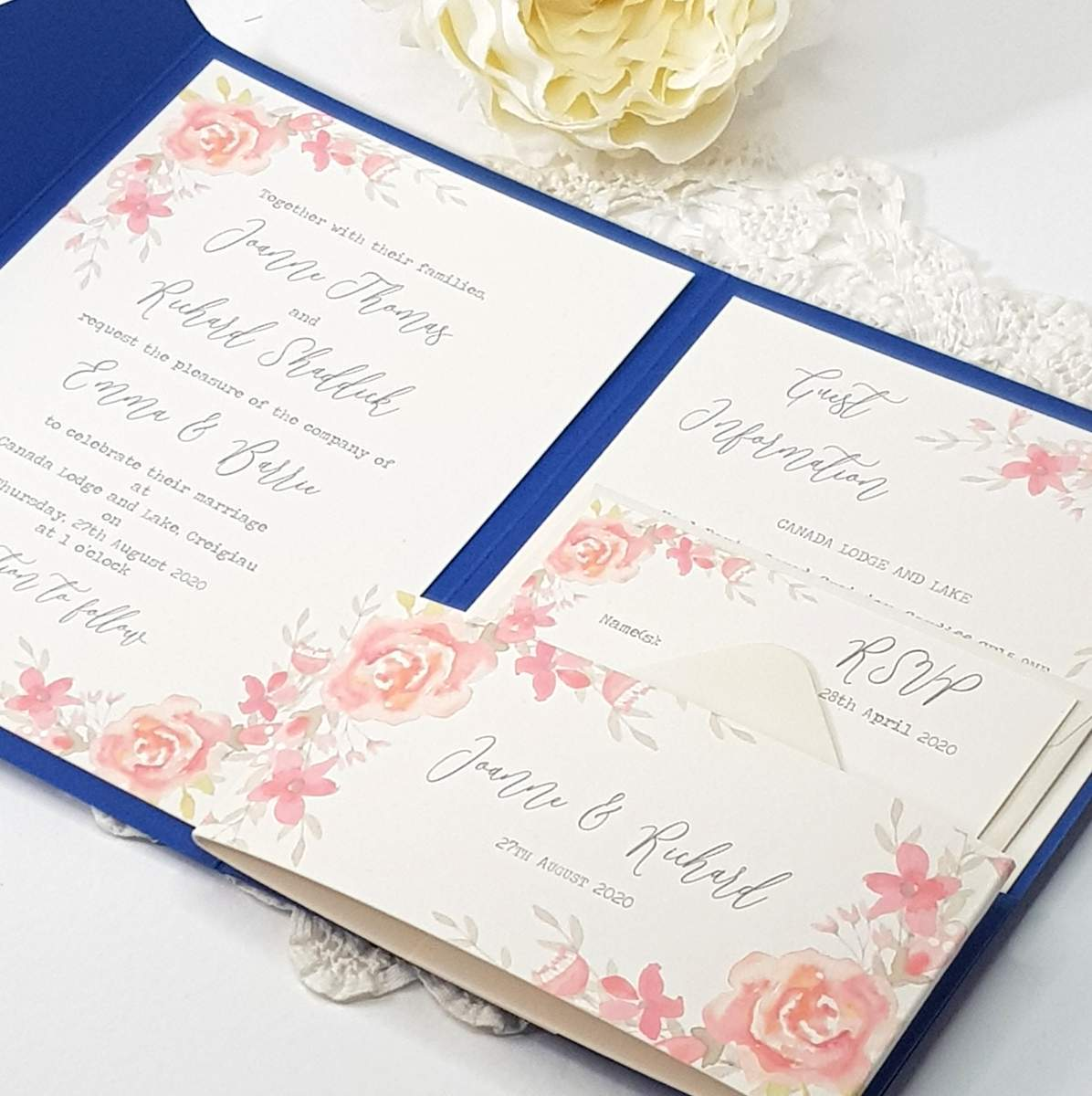 A pretty pocketfold wedding invitation in bright blue with a watercolour floral design of coral pink roses