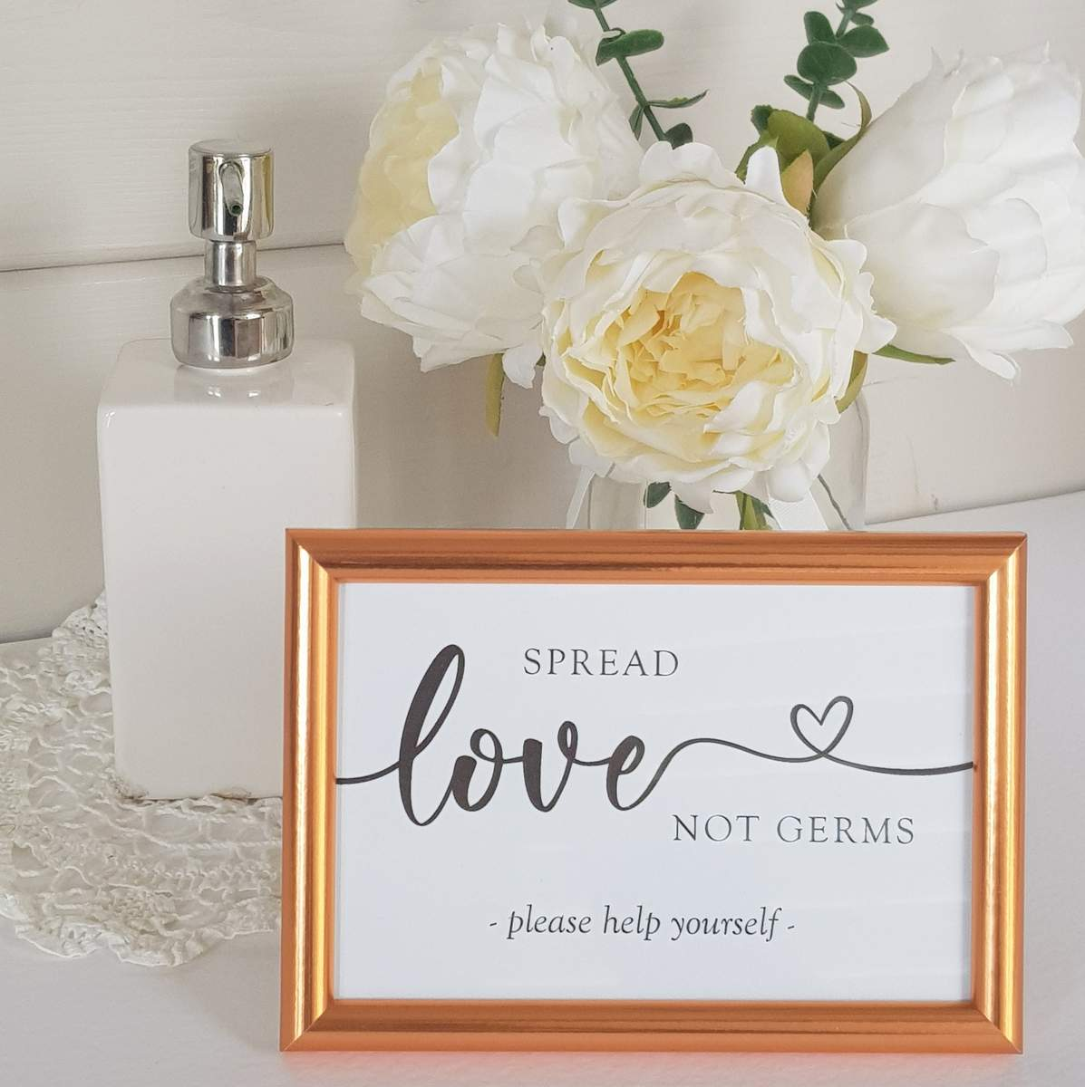 A calligraphy style wedding sign saying spread love not germs, please help yourself alongside a pump dispenser containing hand sanitiser