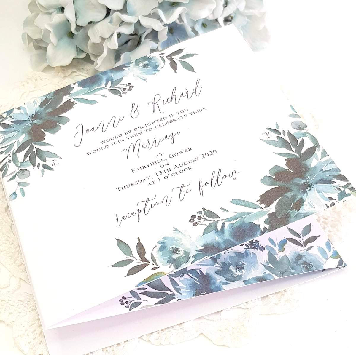 A concertina style wedding invitation with a bold blue floral design, printed onto white recycled card