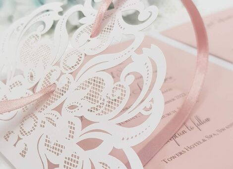pretty blush pink wedding invitation with white lace laser cut detail