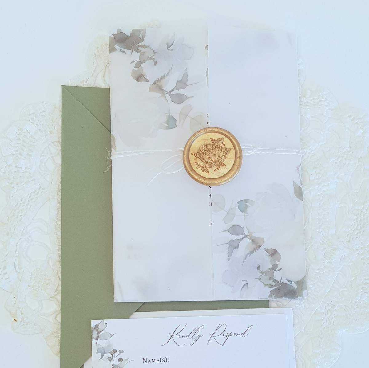 Wedding invitation with a floral printed vellum jacket tied around with twine and a gold wax seal