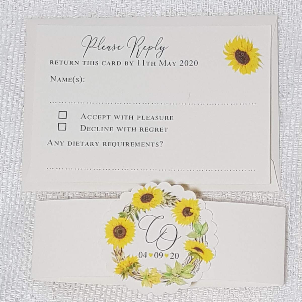 a wedding reply card with a sunflower design, alongside a matching invitation bellyband