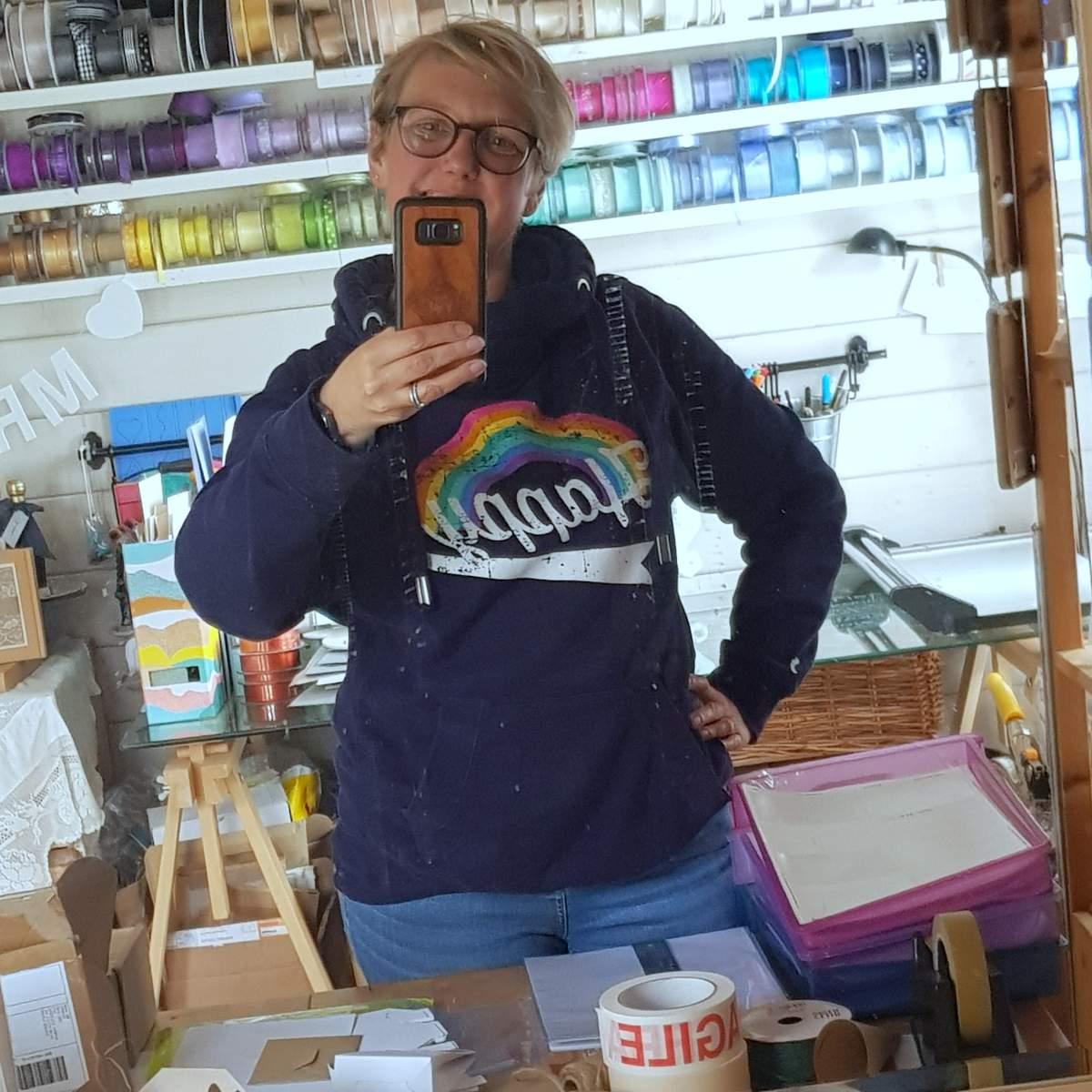 Jo, wearing a rainbow design hoody, taking a mirror selfie in her wedding stationery studio