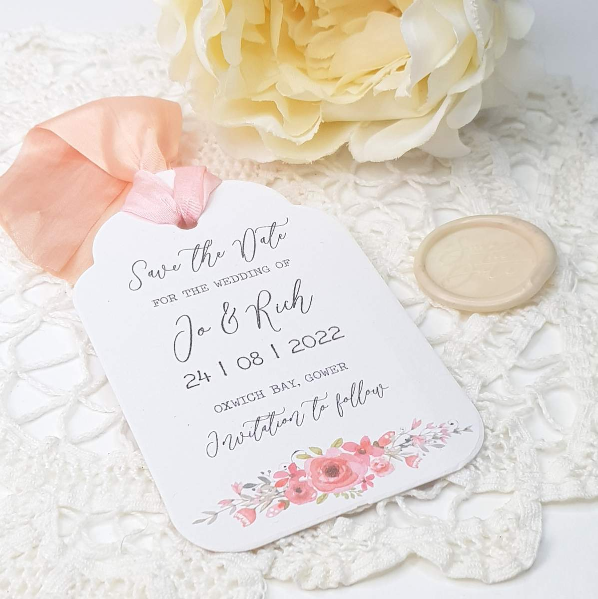wedding save the date card, luggage tag style with pink roses at the bottom and silk ribbon at the top