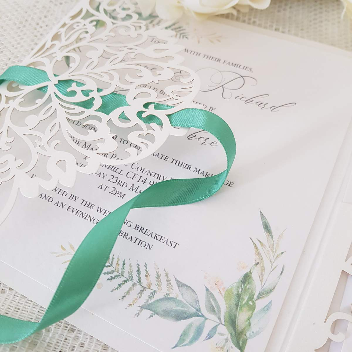 laser cut wedding invitation detail with sage green ribbon and a greenery leaf print design