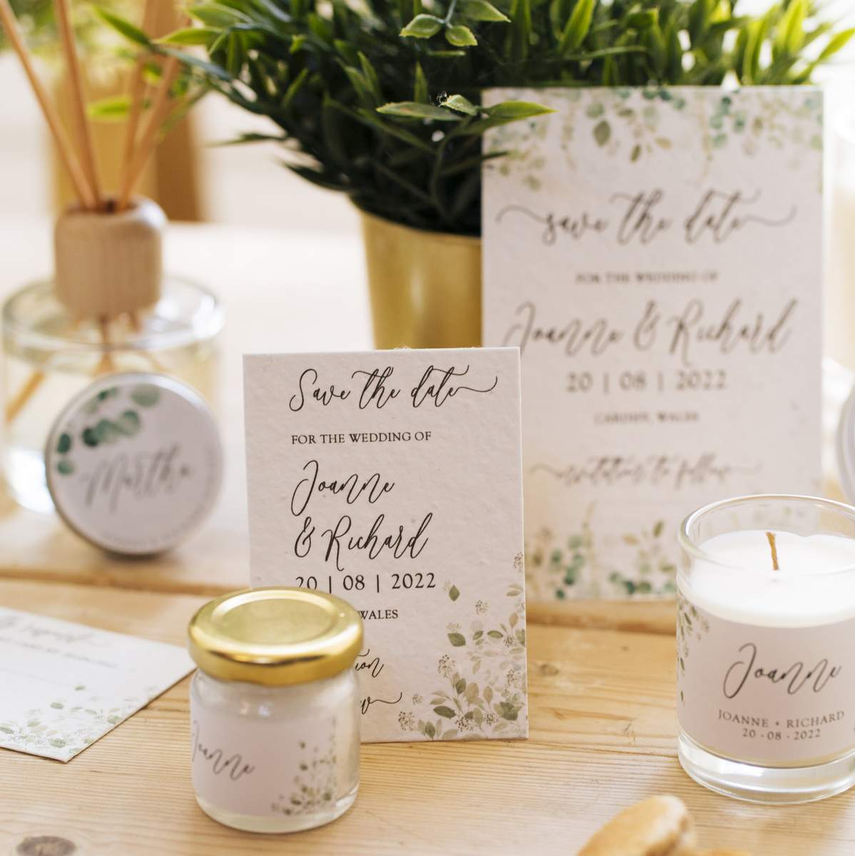 a collection of plastic free eco friendly wedding stationery and favours with a pretty greenery foliage design